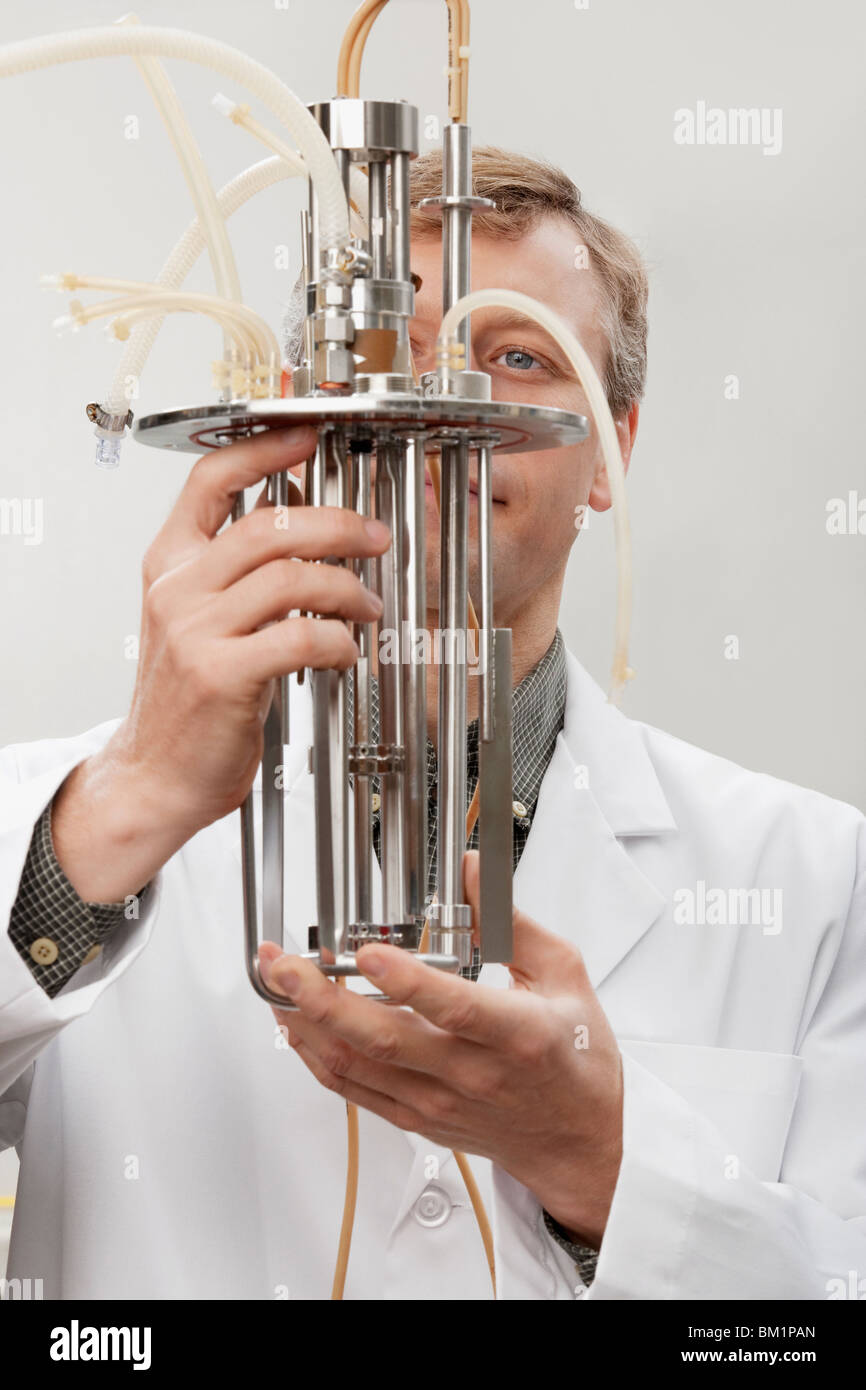 Scientist working on a bioreactor headplate with mixer assembly and methanol sensor probe - Stock Image