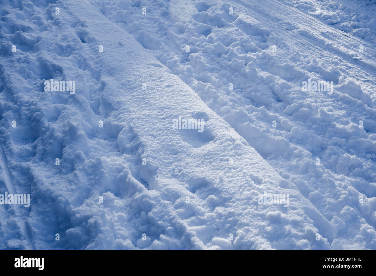 Freshly trampled snow with tyre tracks and footprints. - Stock Image
