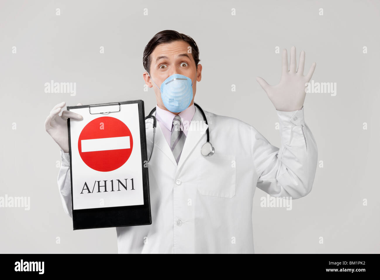 Doctor wearing a flu mask and showing Do Not Enter sign - Stock Image