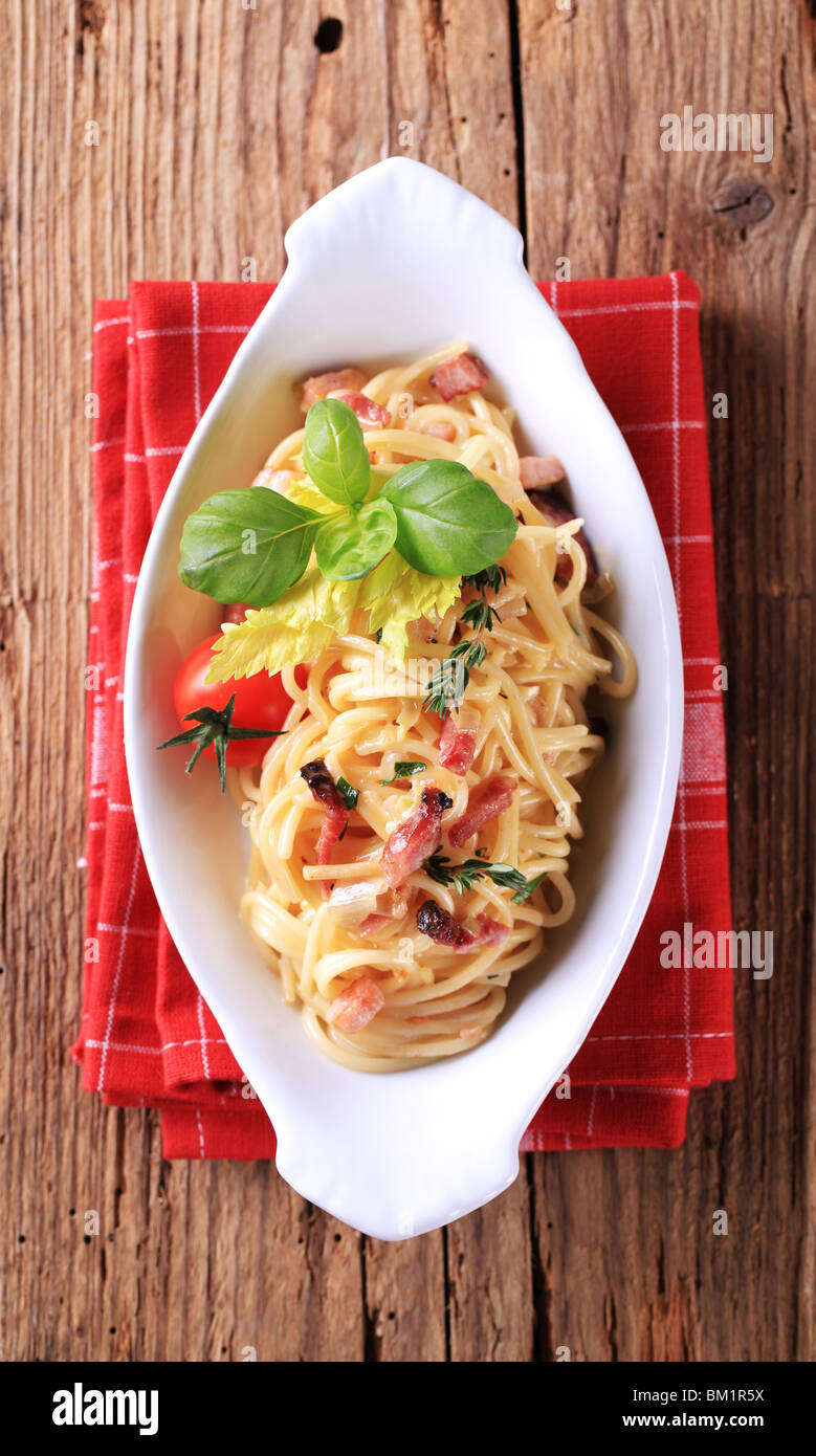 Bowl of spaghetti with bacon, onion and egg - Stock Image