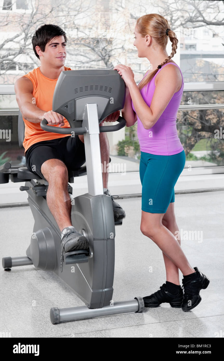 Woman talking to a man working out on an exercise machine in a gym - Stock Image