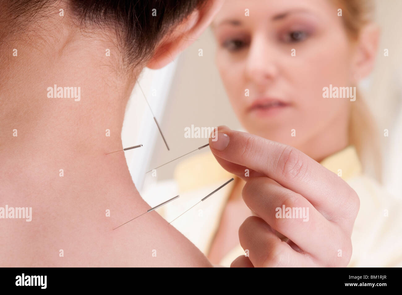 Acupuncturist applying needles on a person's back - Stock Image