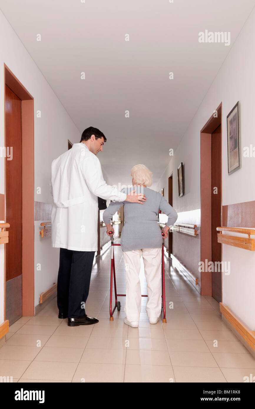 Doctor assisting a woman in walking - Stock Image