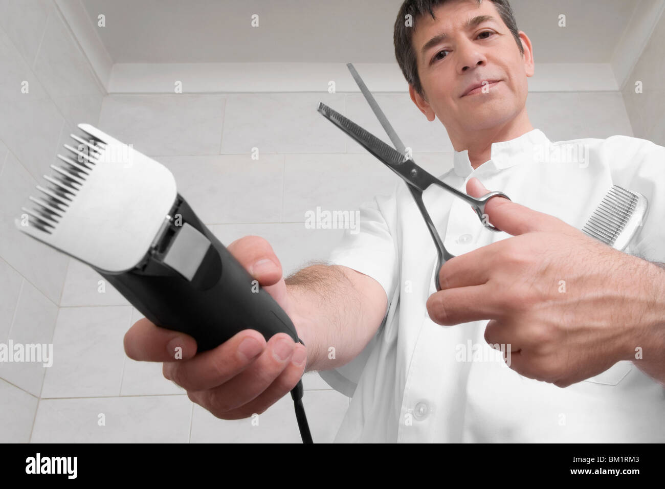 Vet holding an electric razor and scissors - Stock Image