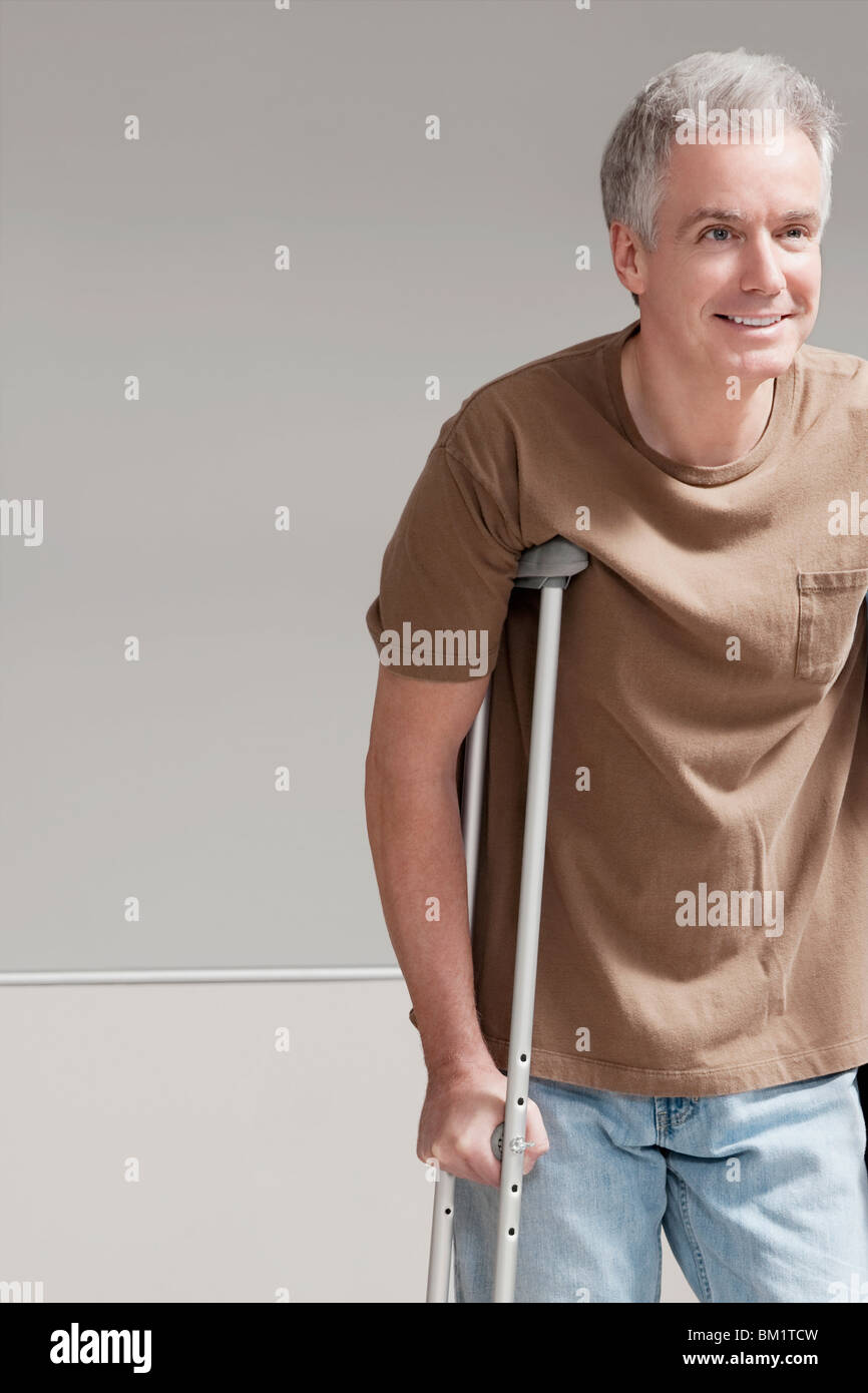 Patient walking with the help of crutches - Stock Image