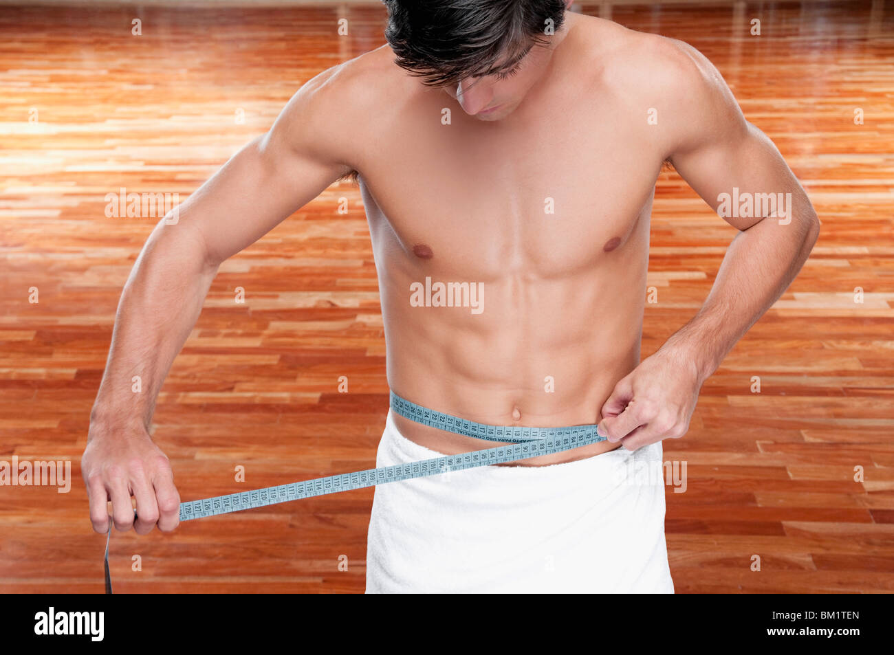 Man measuring his waist with a tape measure Stock Photo
