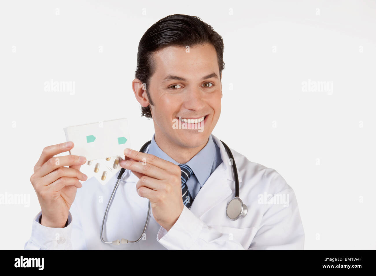 Portrait of a doctor holding a pack of medicine - Stock Image