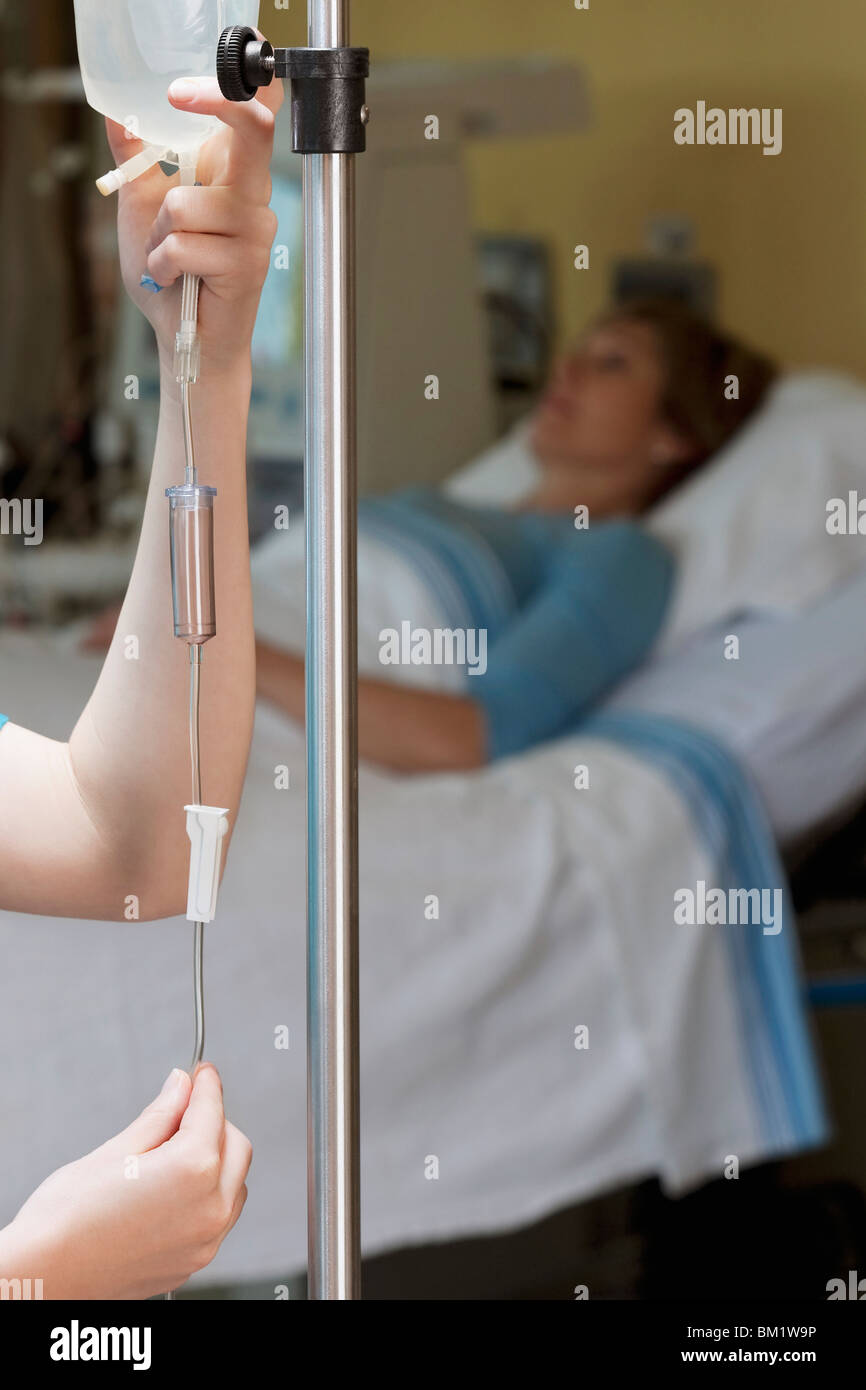 Female doctor checking a saline drip - Stock Image