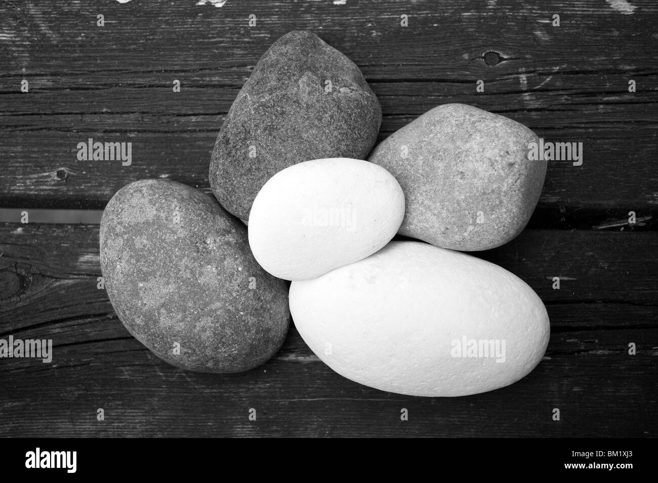 A Black & White image of five beach pebbles on old wooden planks - Stock Image