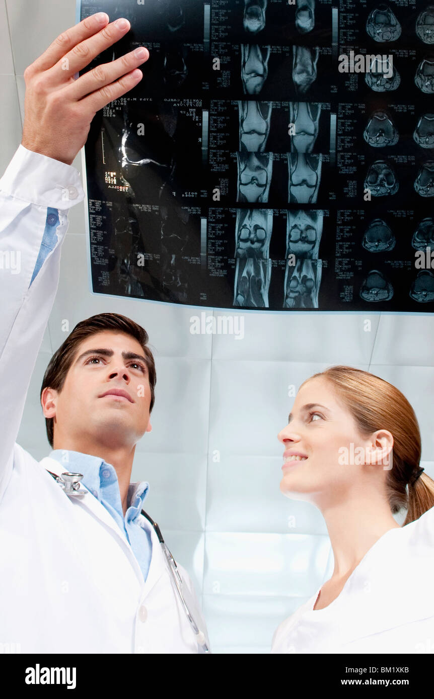 Doctor and a female nurse examining an x-ray report - Stock Image