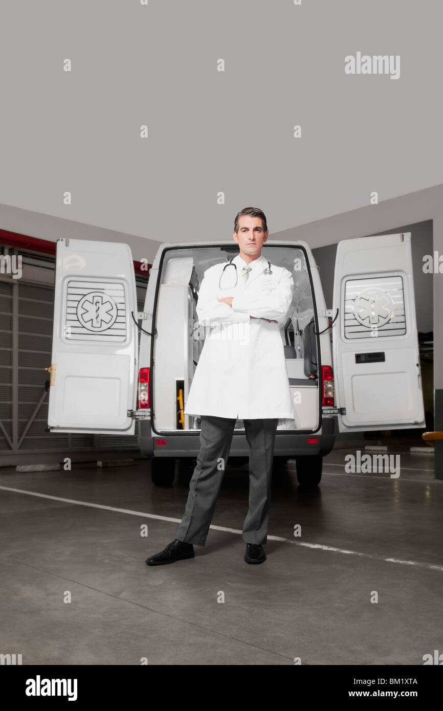 Doctor standing with an ambulance behind him - Stock Image