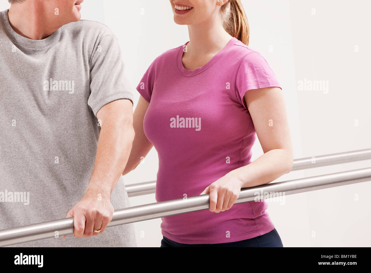 Physiotherapist assisting a patient in walking - Stock Image