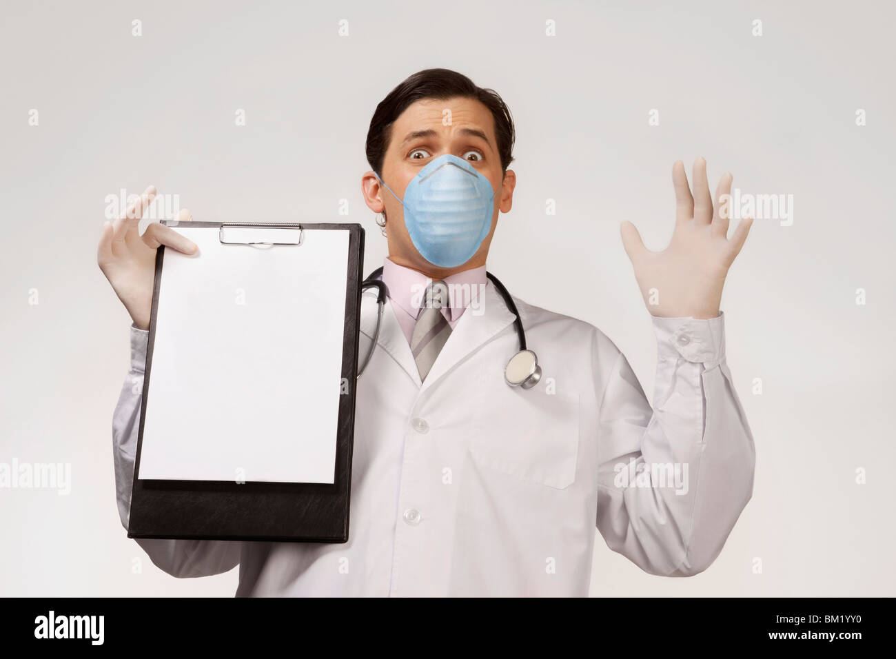 Doctor wearing a flu mask and showing a clipboard - Stock Image