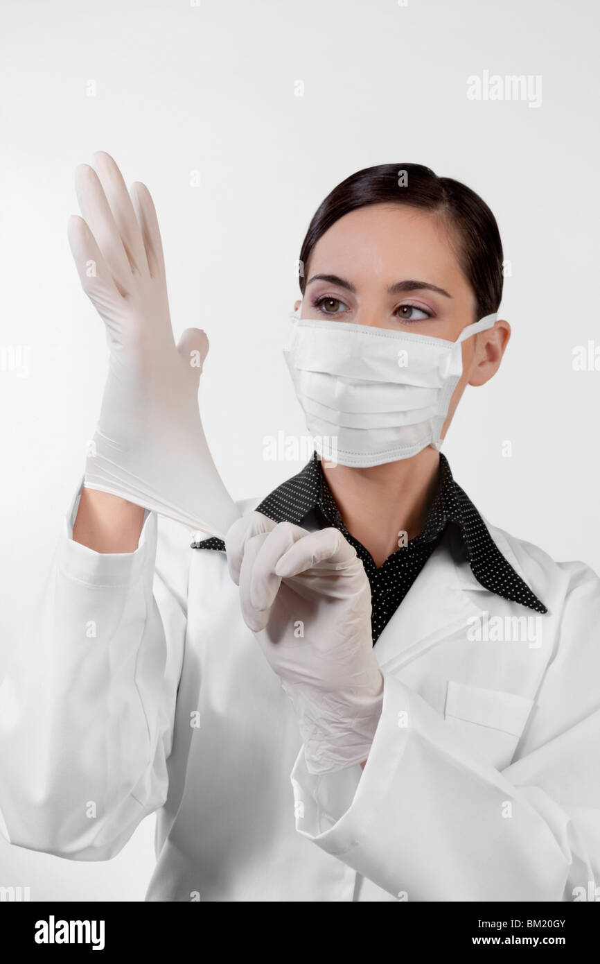 Female doctor putting on surgical gloves - Stock Image