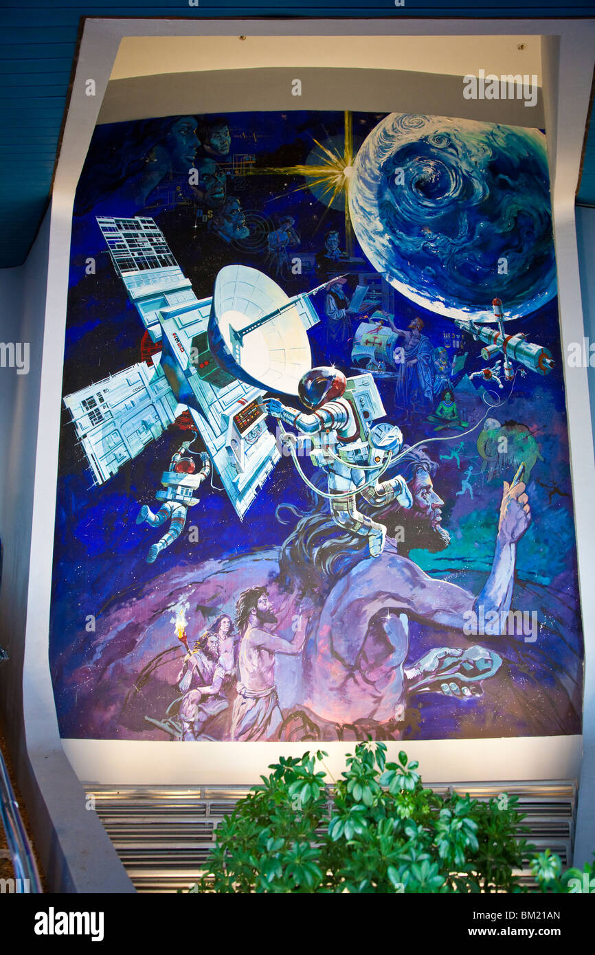 Painted panel shows evolution of man from caveman to space explorer near entrance to Spaceship Earth at Epcot Center - Stock Image