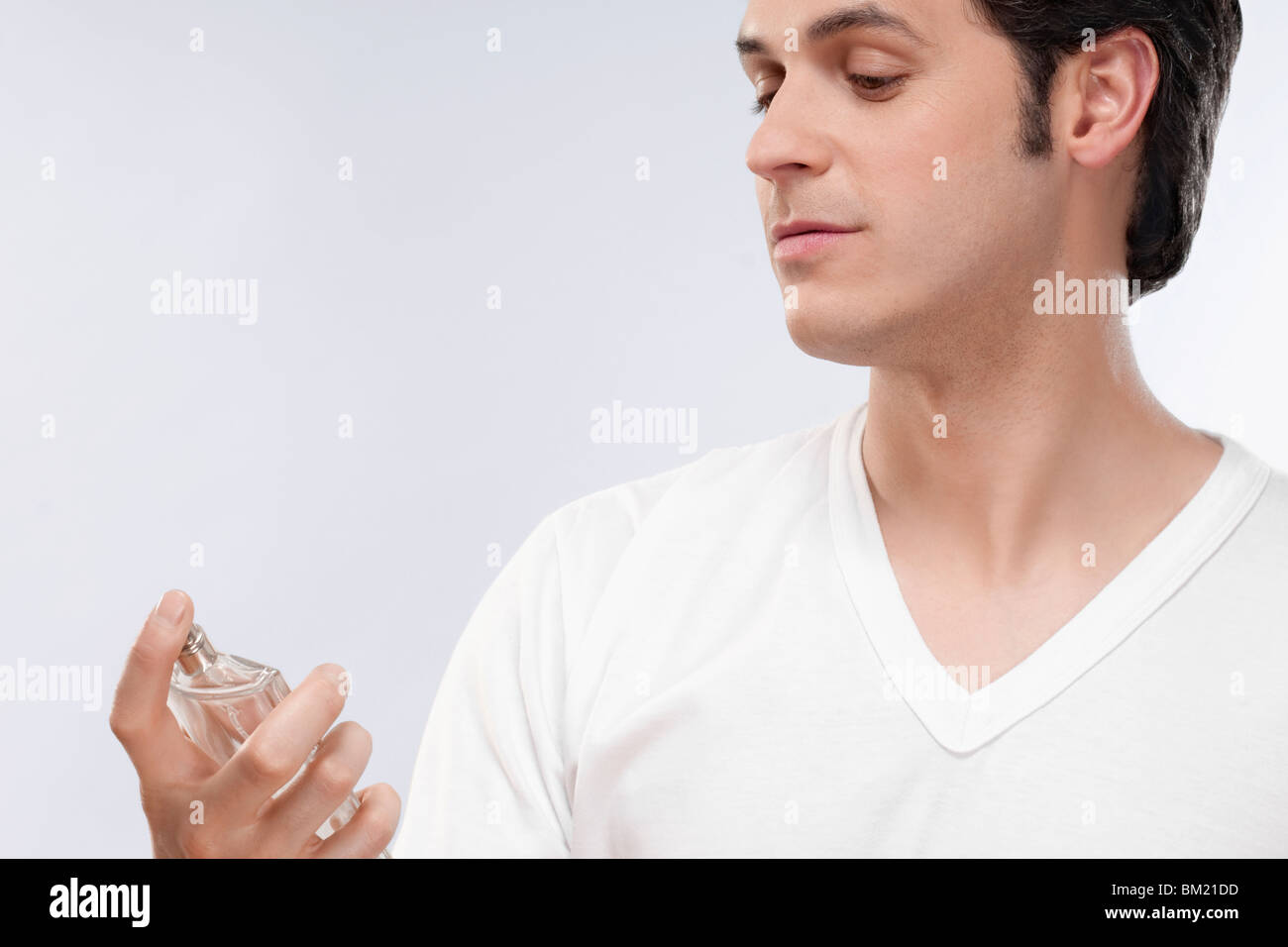 Man looking at a perfume bottle - Stock Image