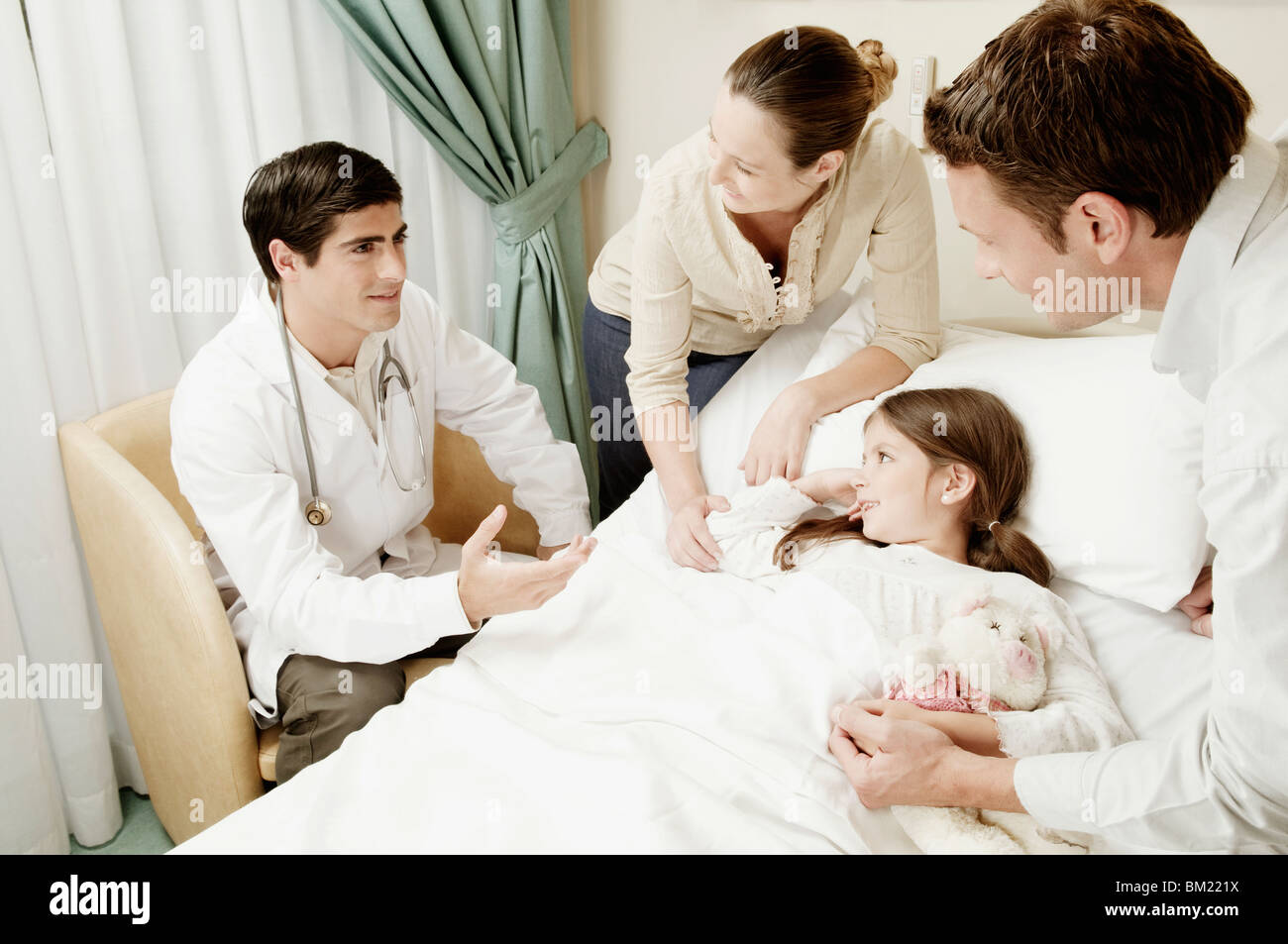 Girl on a hospital bed and her parents discussing with a doctor - Stock Image
