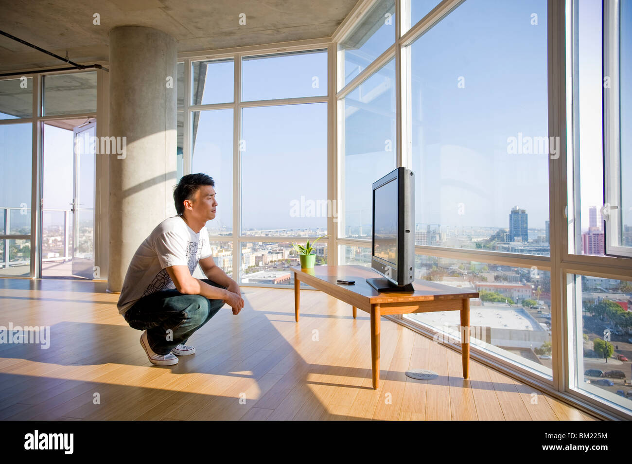 young man watching television in a spacious apartment san diego