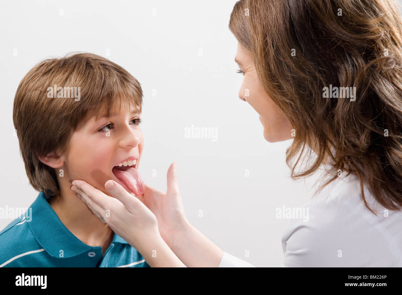 Female doctor examining a boy - Stock Image