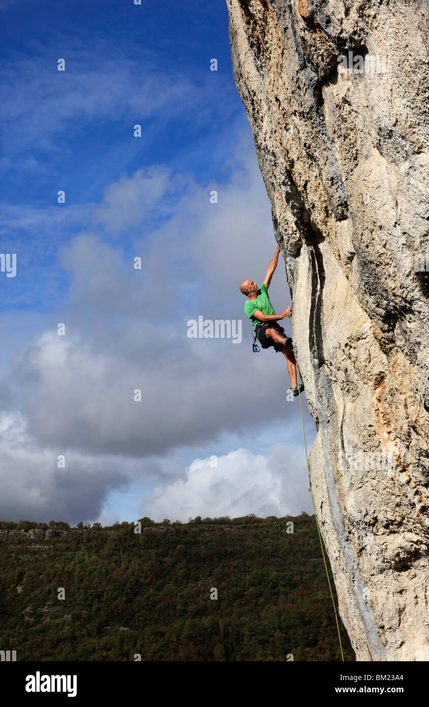 A climber tackles a steep and challenging route on the cliffs of the Aveyron Gorge, Aveyron region, Massif Central, - Stock Image