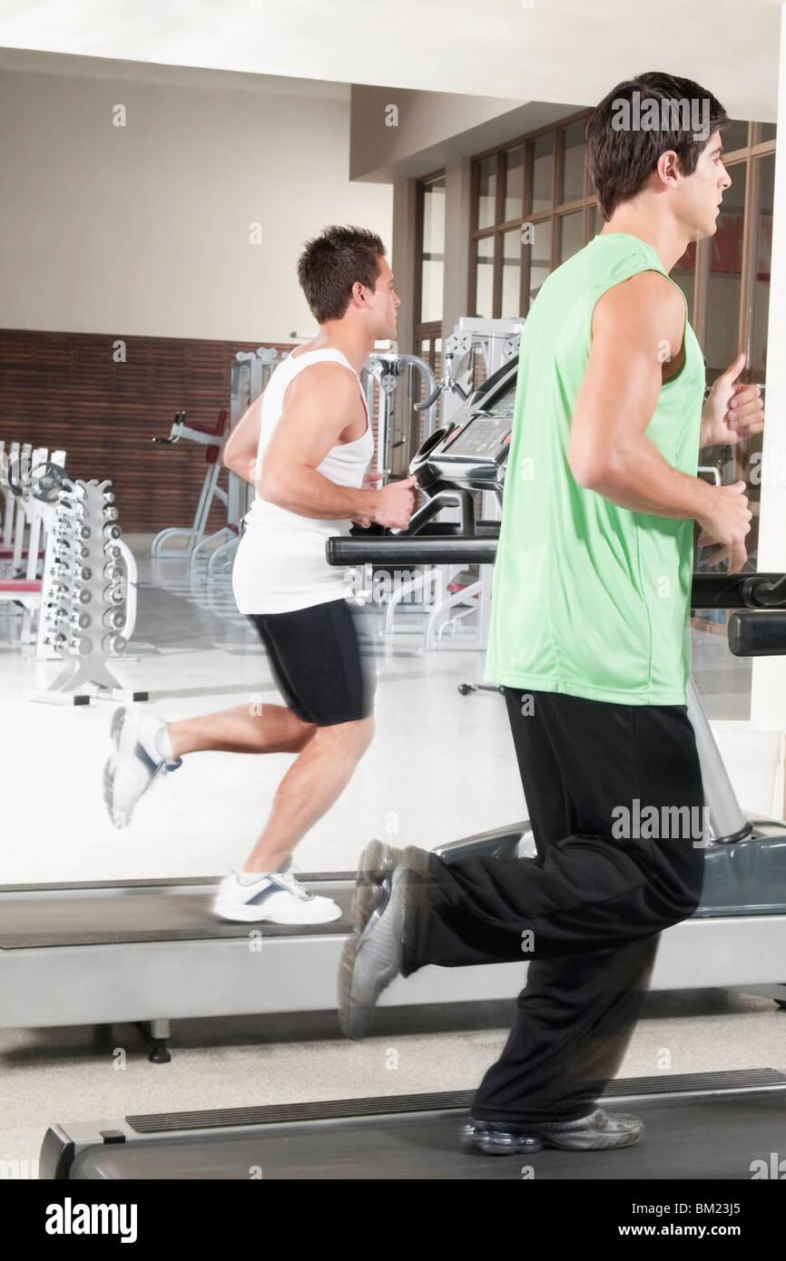 Two men running on treadmills - Stock Image