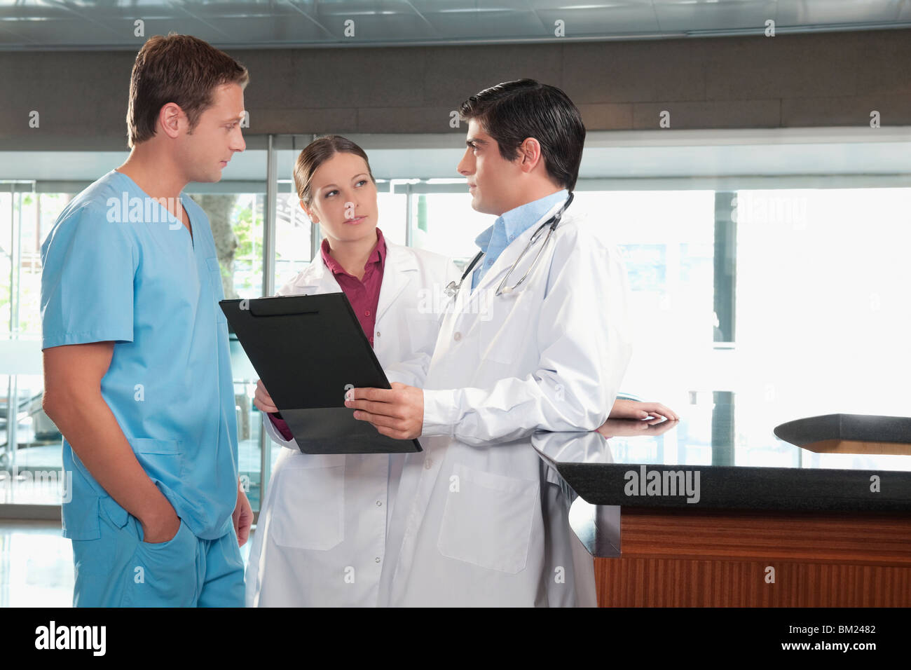 Three doctors discussing a medical report - Stock Image