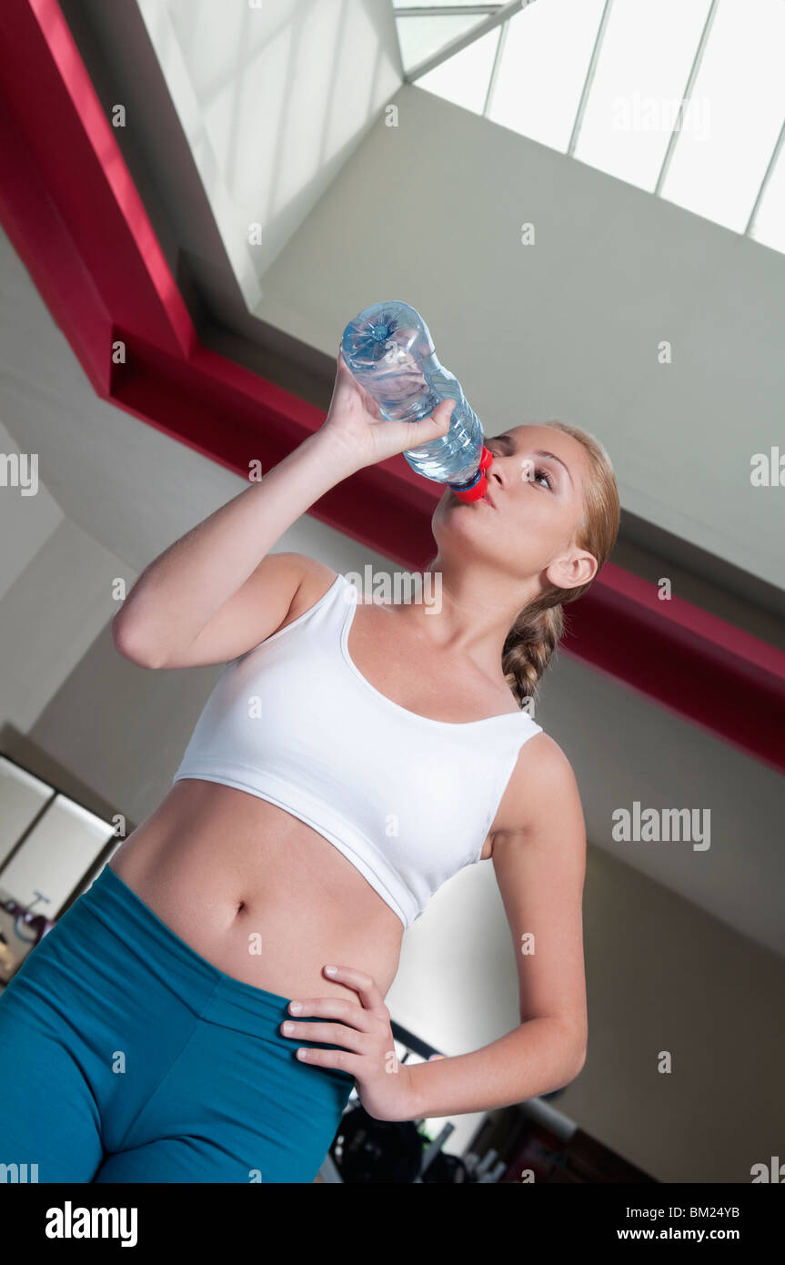 Woman drinking water from a water bottle in a gym - Stock Image