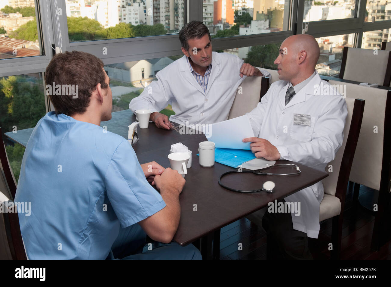 Doctors discussing in a cafeteria - Stock Image