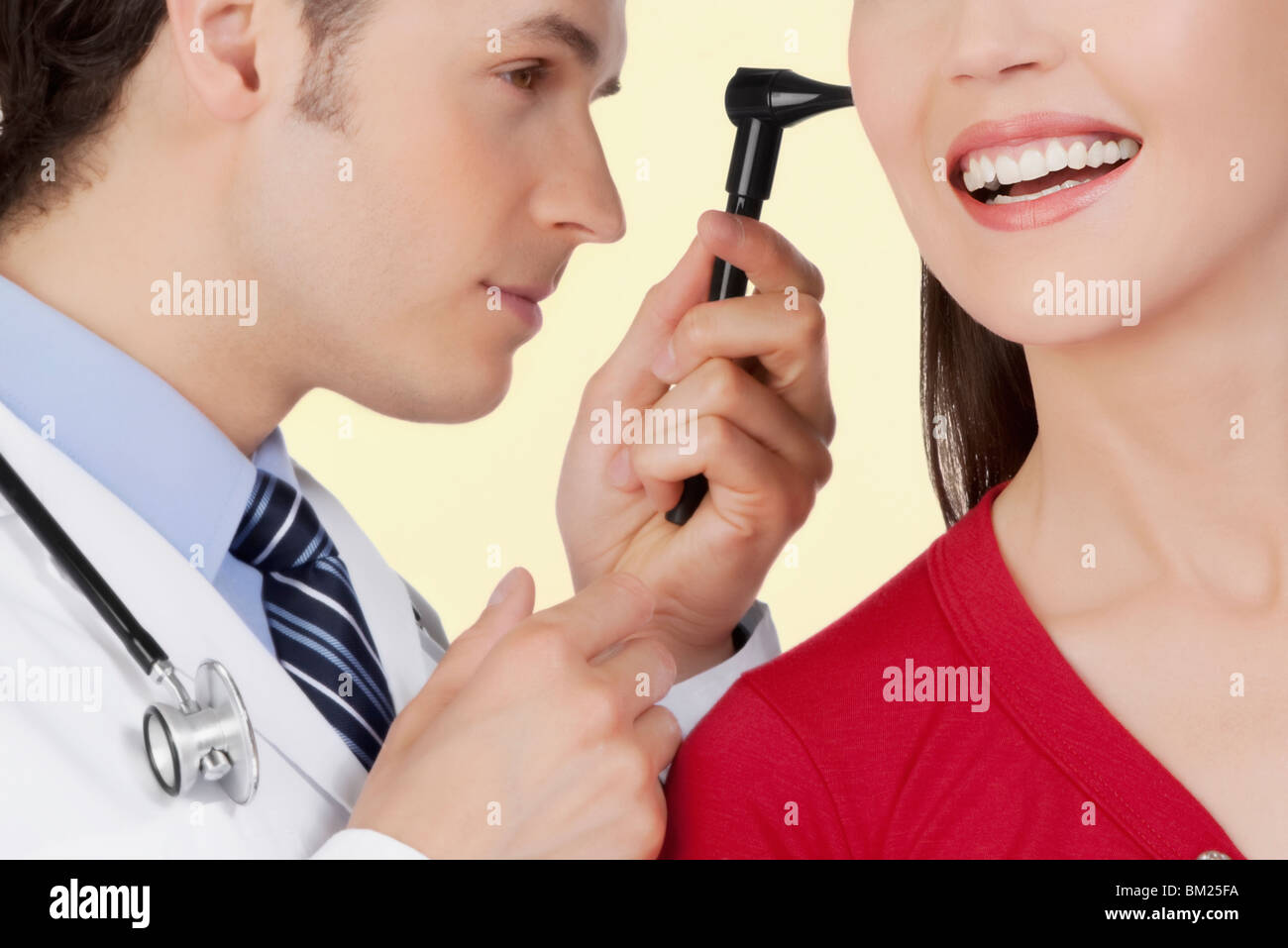 Doctor examining a woman's ear with an otoscope - Stock Image