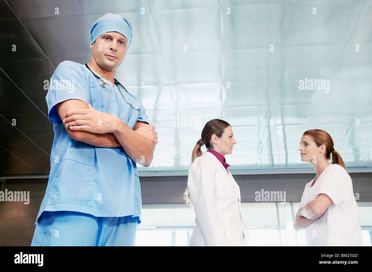 Male surgeon standing with his colleagues discussing in the background - Stock Image