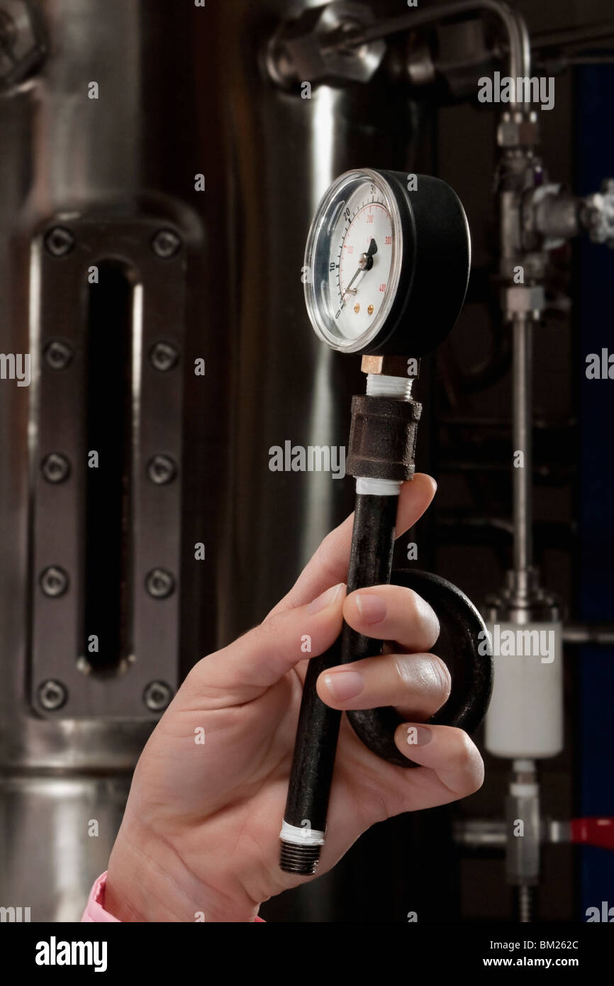Female doctor holding a pressure gauge in a laboratory - Stock Image