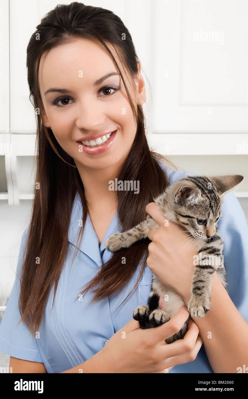 Female vet carrying a cat and smiling - Stock Image