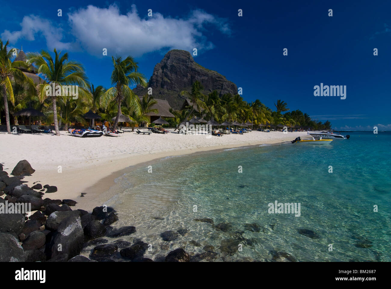 Sun loungers on the beach and Mont Brabant (Le Morne Brabant), UNESCO World Heritage Site, Mauritius, Indian Ocean - Stock Image