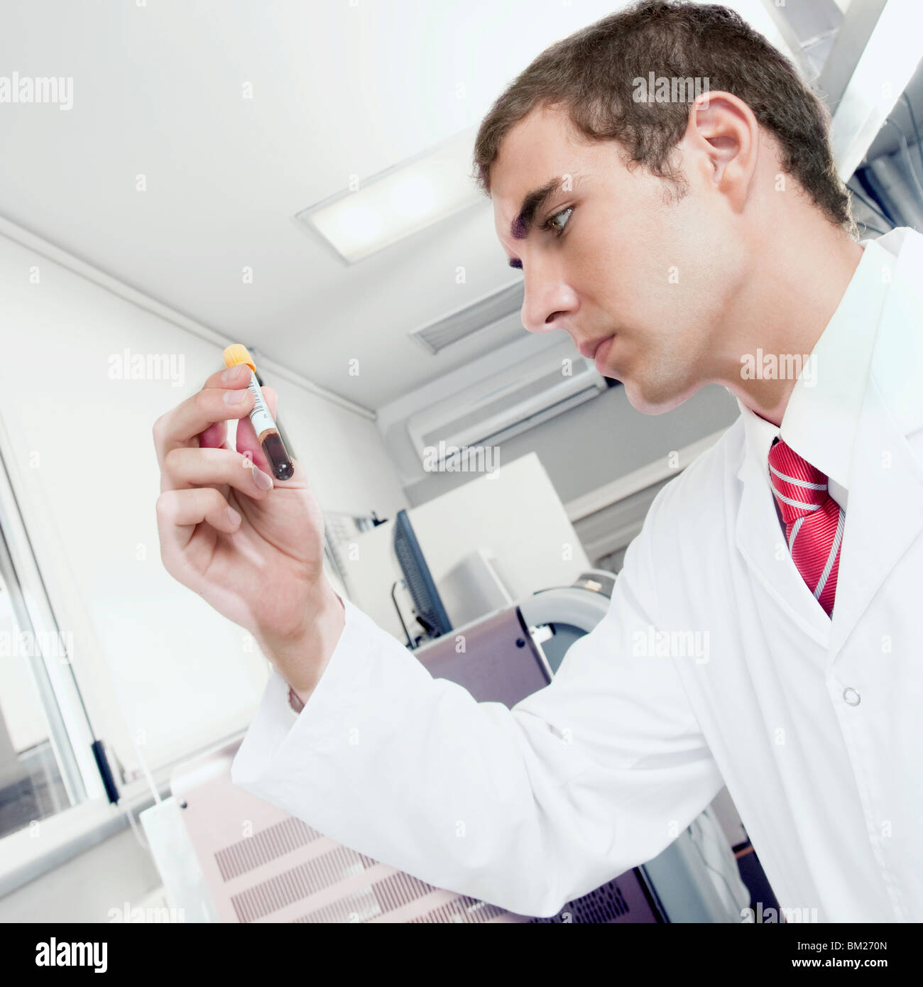 Lab technician testing a blood sample in a test tube - Stock Image