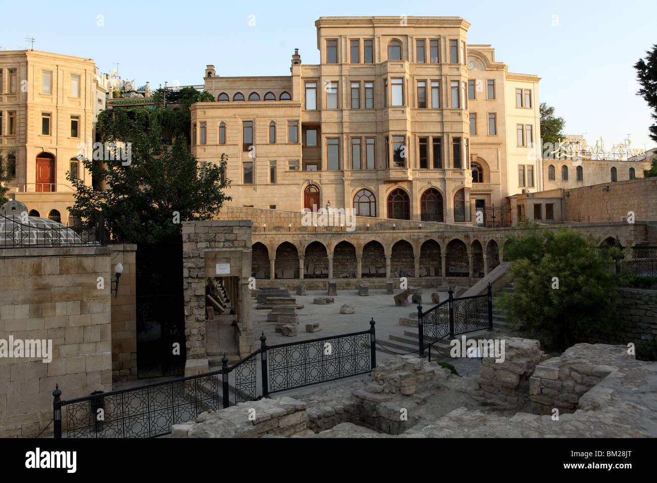 Sun rises on the hammam and markets near the Maiden Tower in the historical walled old city of Baku in Azerbaijan. - Stock Image