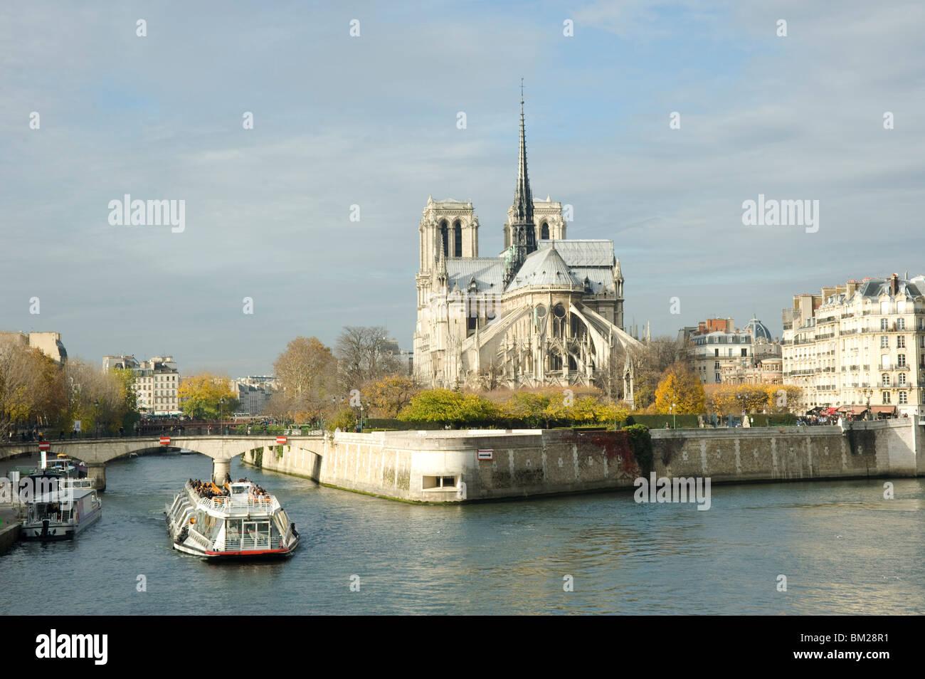 A bateau mouche passing the Ile de La Cite and Notre Dame Cathedral in autumn, Paris, France - Stock Image