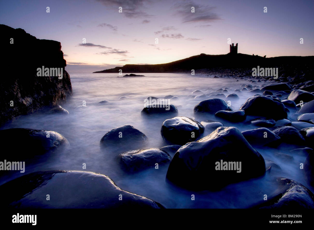 View across the Rumble Churn at dawn towards the ruins of Dunstanburgh Castle, Embleton Bay, Northumberland, UK Stock Photo