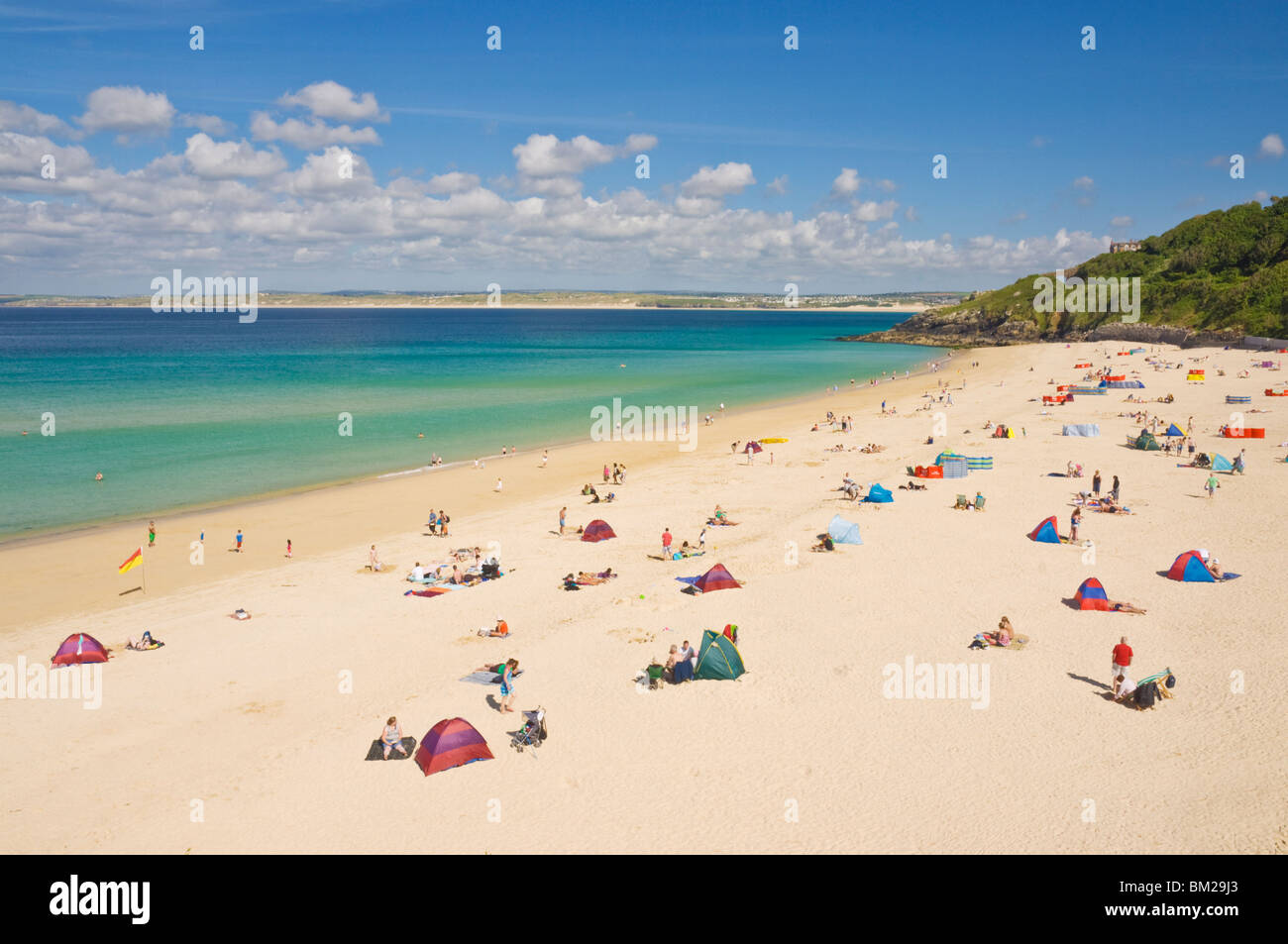 Holidaymakers and tourists sunbathing on Porthminster beach, St. Ives (Pedn Olva), North Cornwall, UK - Stock Image