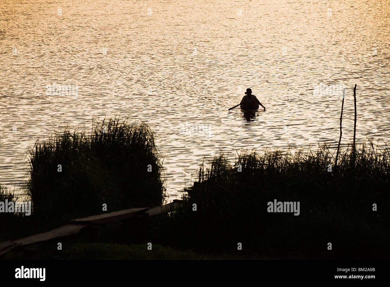 Man paddling small boat on Crocodile Lake at sunset in Cat Tien National Park. - Stock Image