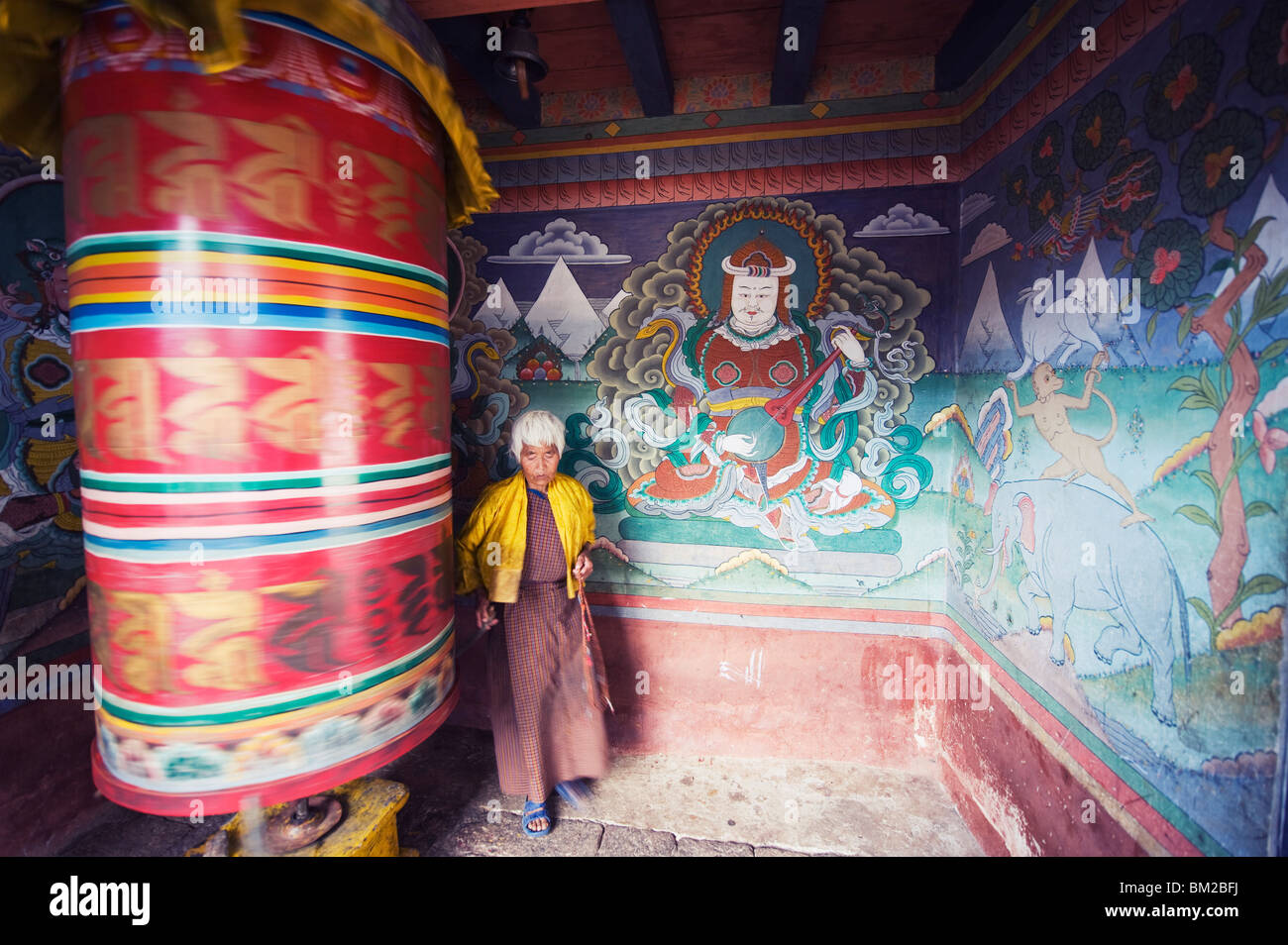 A woman spinning a prayer wheel, Chimi Lhakhang dating from 1499, Temple of the Divine Madman Lama Drukpa Kunley, - Stock Image