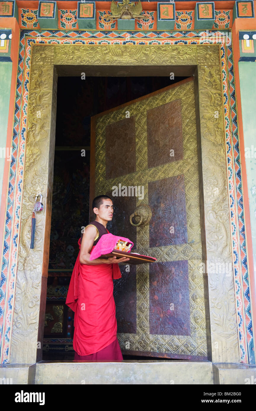 Young monk at a temple doorway, Khamsum Yuelley Namgyal Chorten built in 1999, Punakha, Bhutan - Stock Image