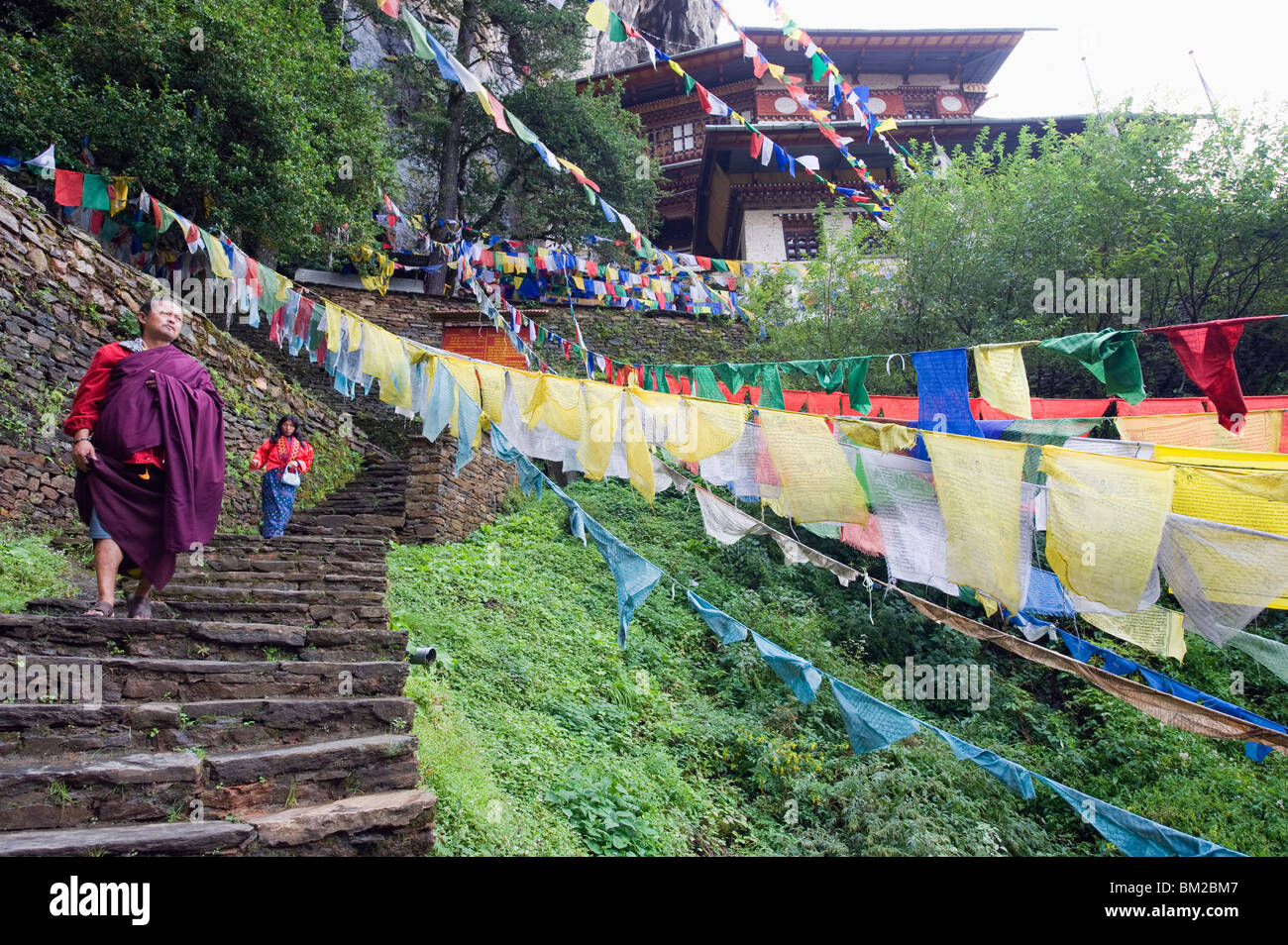 A monk walking through prayer flags, Tigers Nest, Taktsang Goemba, Paro Valley, Bhutan - Stock Image