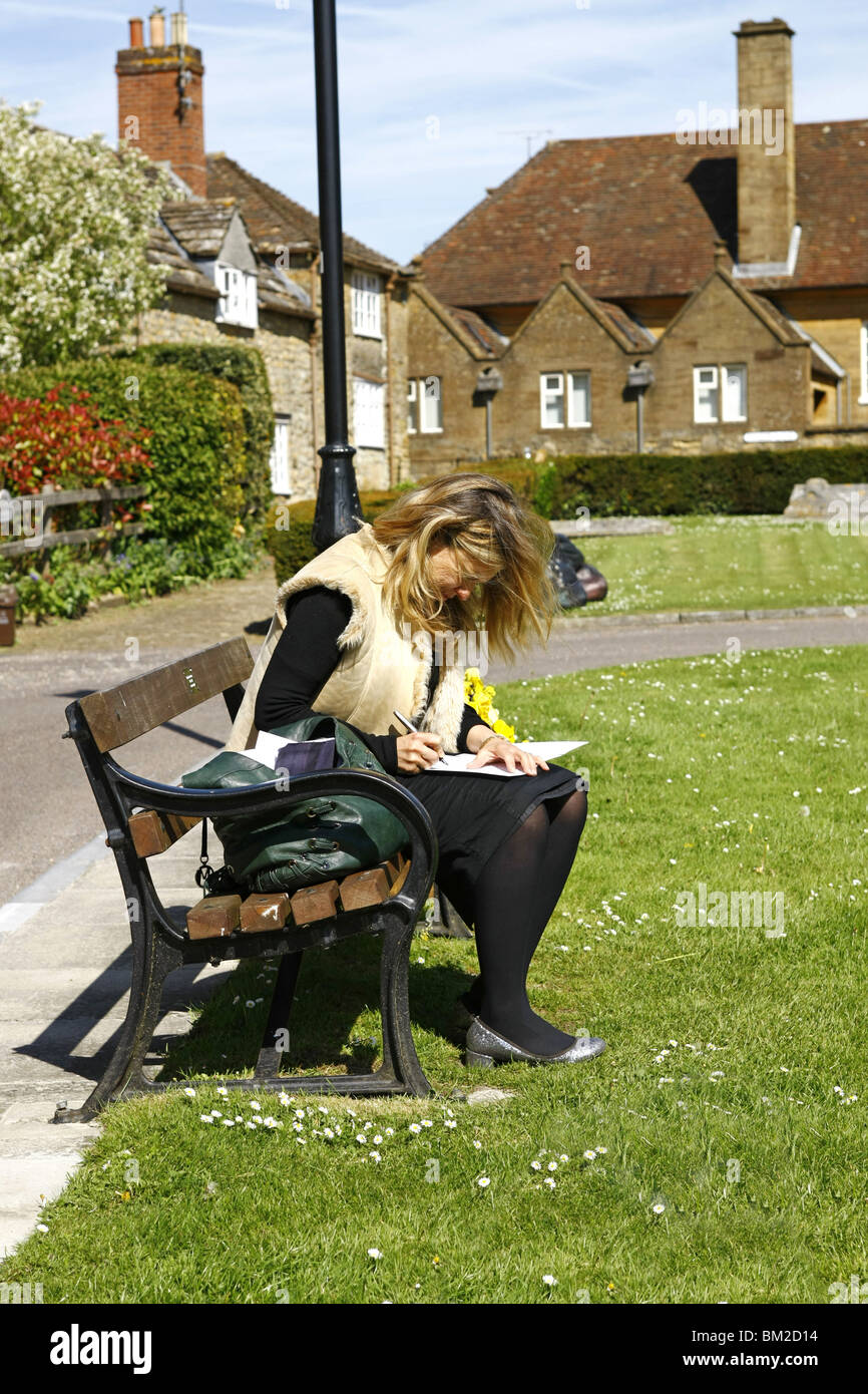 A young woman sits on a park bench in the sunshine writing a message in a Get Well Soon card to her friend. - Stock Image