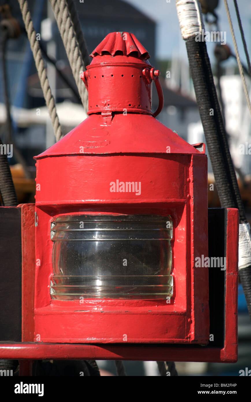 Red port lantern in sunlight on old ship, Plymouth, Devon, UK - Stock Image