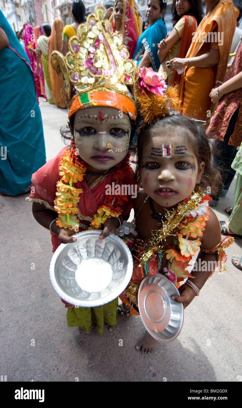 Two street children dressed in the style of Krishna at Diwali festival time, begging, Udaipur, Rajasthan, India - Stock Image