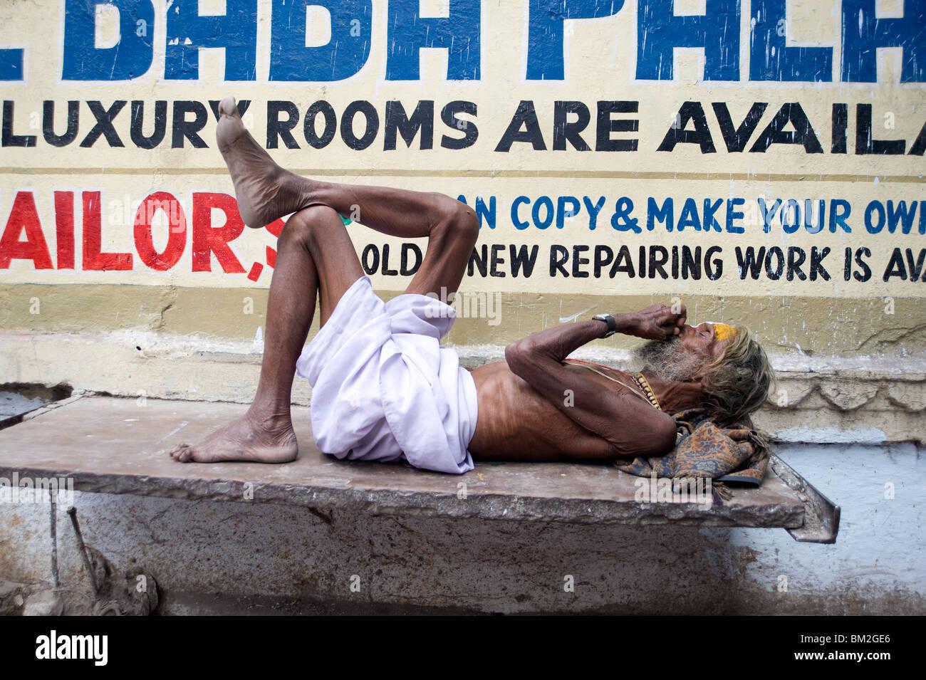 Holy man (Saddhu) resting on a marble slab, Udaipur, Rajasthan, India - Stock Image