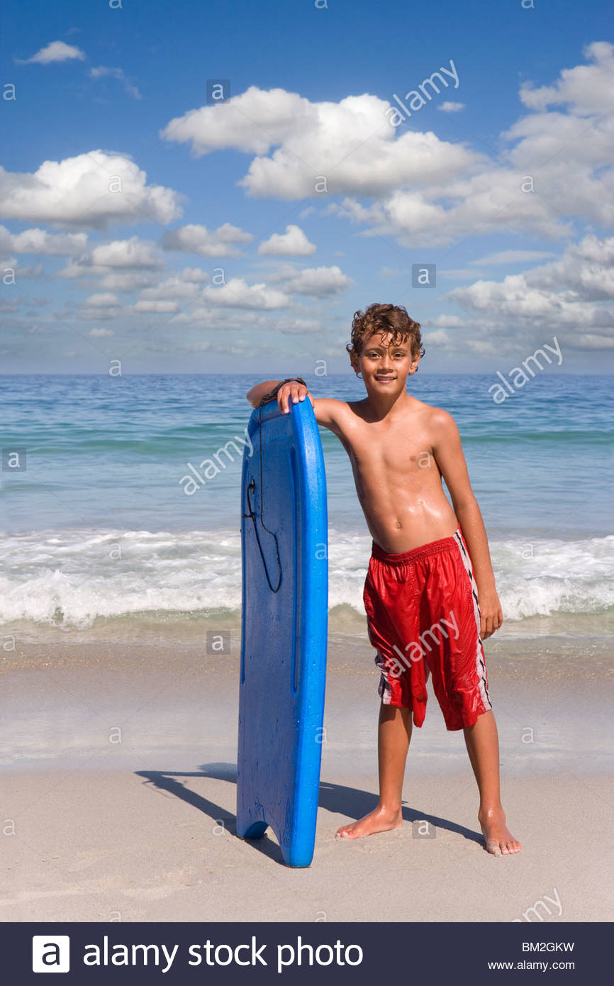 Boy standing on beach near ocean with body board - Stock Image