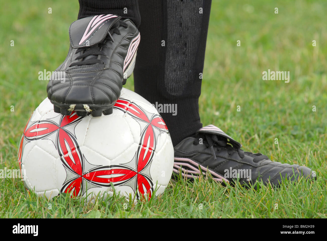 Close-up image of soccer ball and cleats with grass background - Stock Image