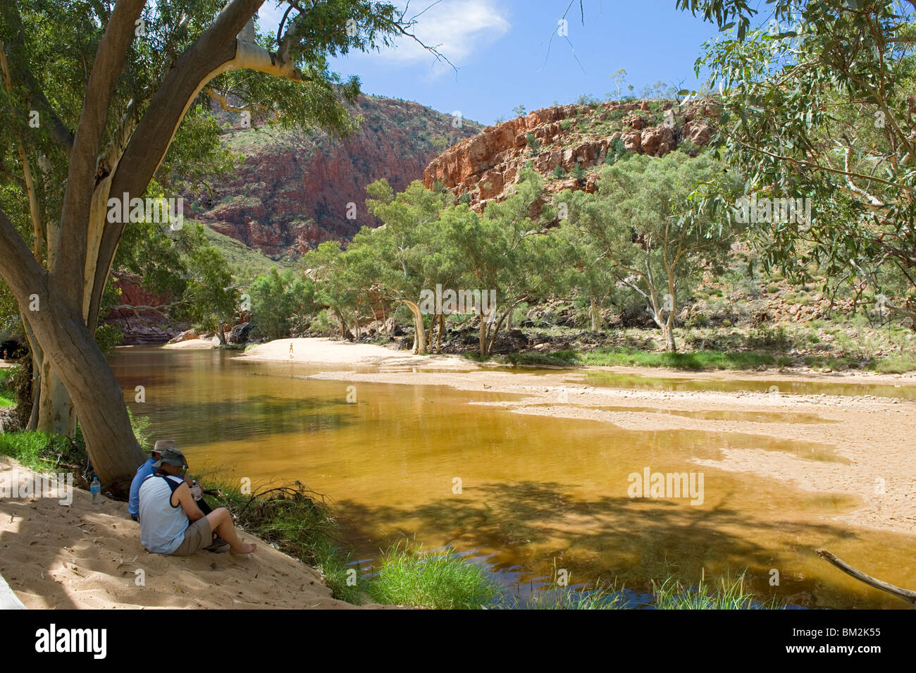 Two people sitting in the shade of trees overlooking the waterhole at Ormiston Gorge in the Western MacDonnell Ranges - Stock Image