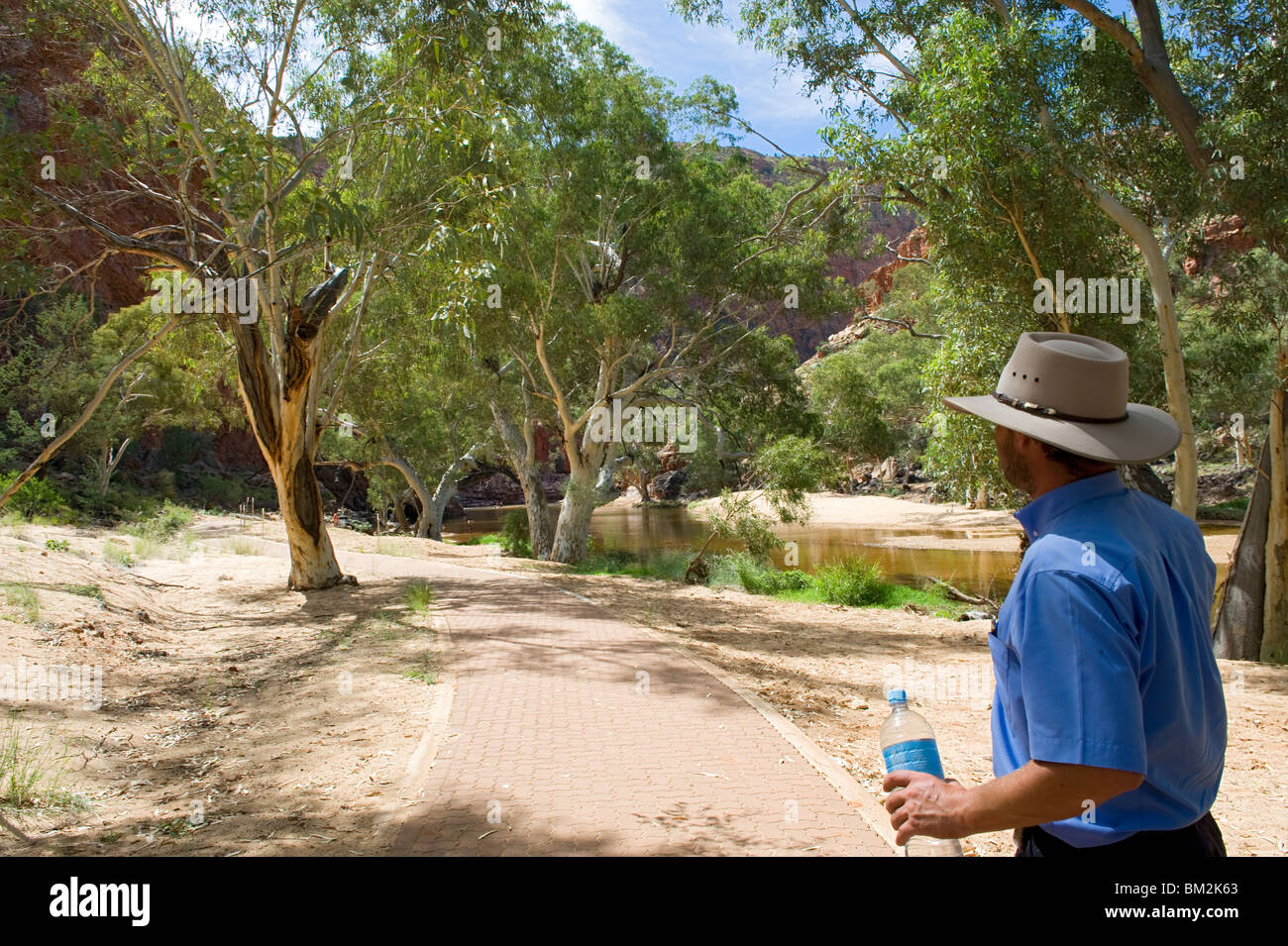 An Australian man with typical hat walking to Ormiston Gorge in the Western MacDonnell Ranges, Northern Territory, - Stock Image